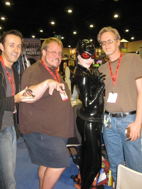 Catwoman posing with 3 of her favorite artists: J. Scott Campbell, Adam Hughes, and Bruce Timm.