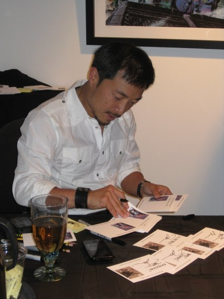 Jim Lee signing for people buying art from the gallery.