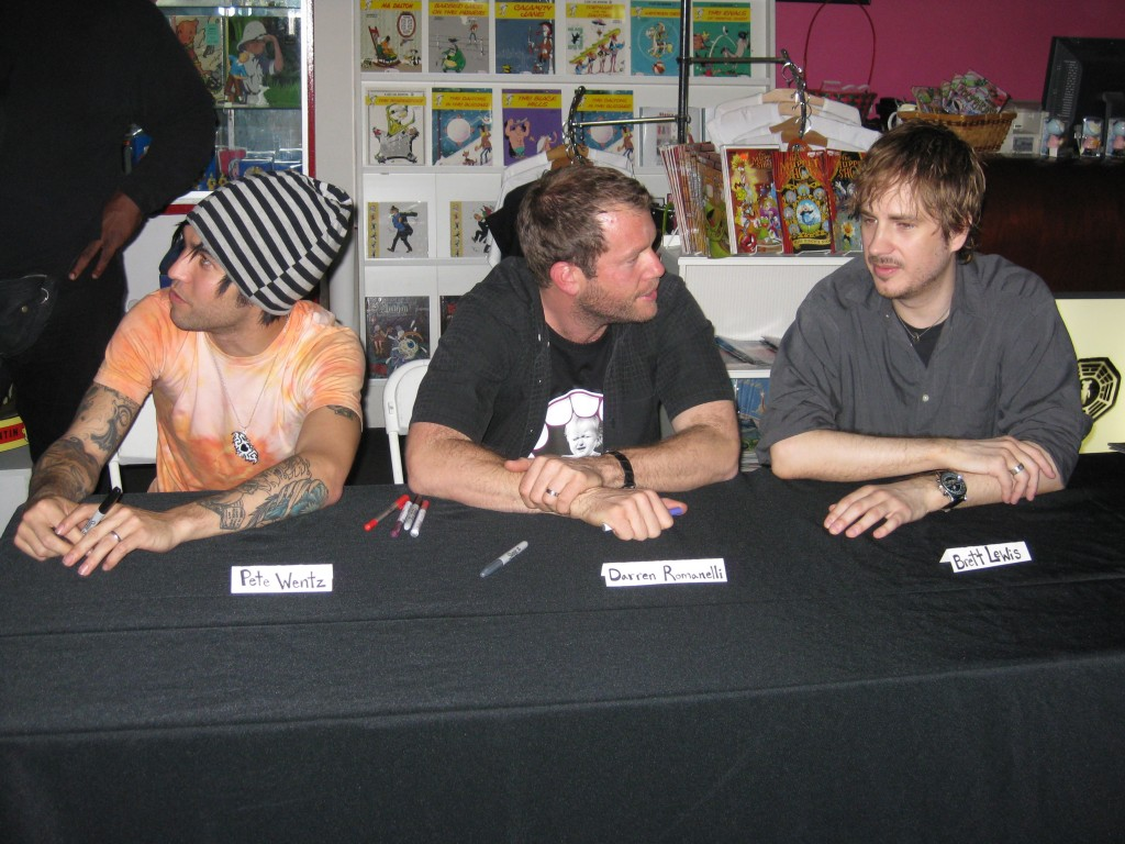 Pete Wentz, Darren Romanelli, and Brett Lewis sit down to prepare for the signing.